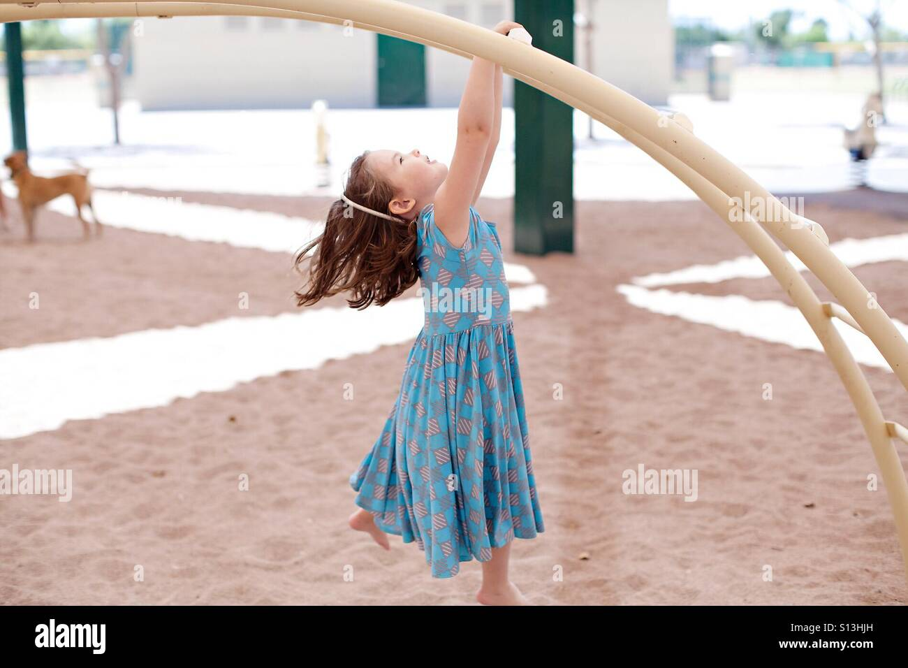Girl hanging from monkey bars at park - Stock Image