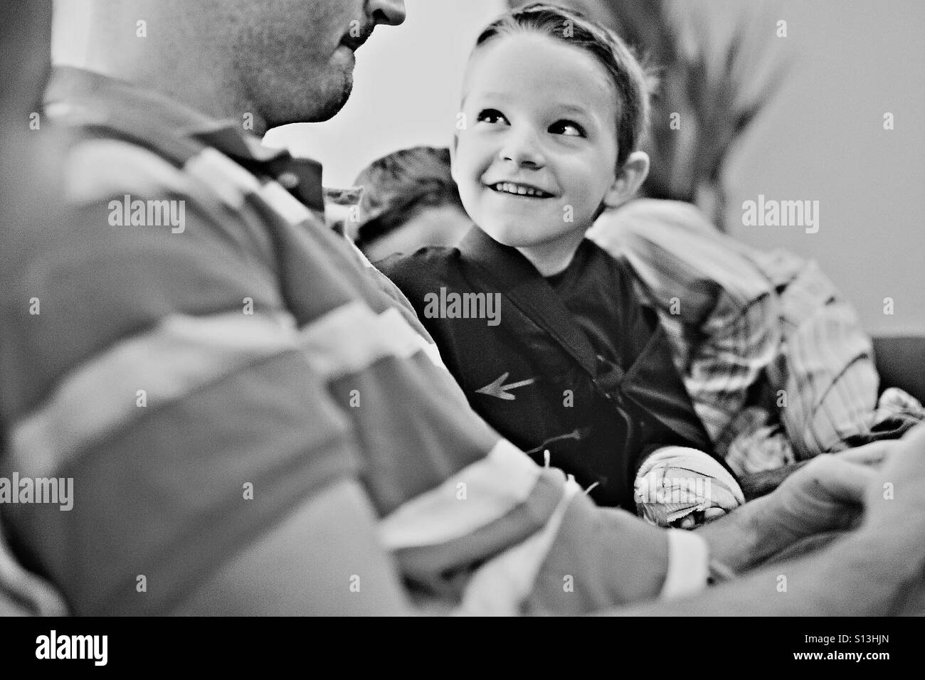 Boy with broken arm looking up and smiling at his dad - Stock Image