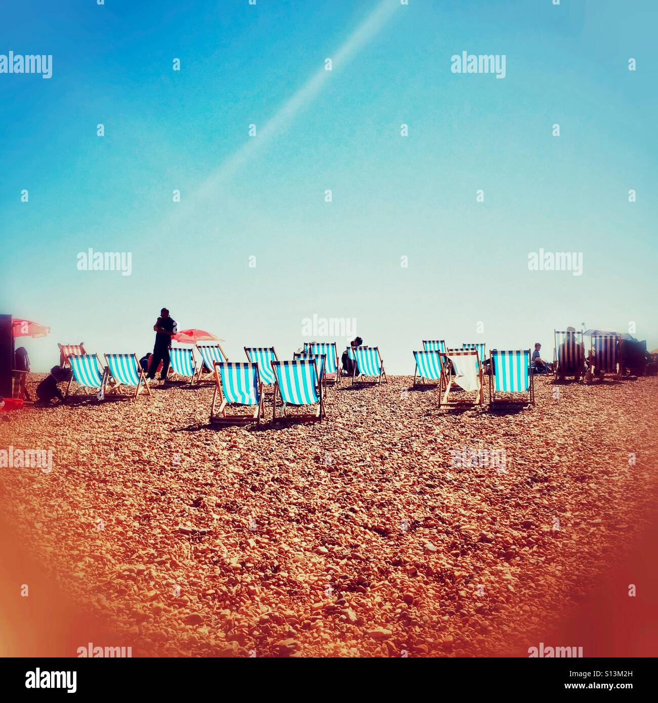 Deckchairs on Brighton beach in the English summer - Stock Image