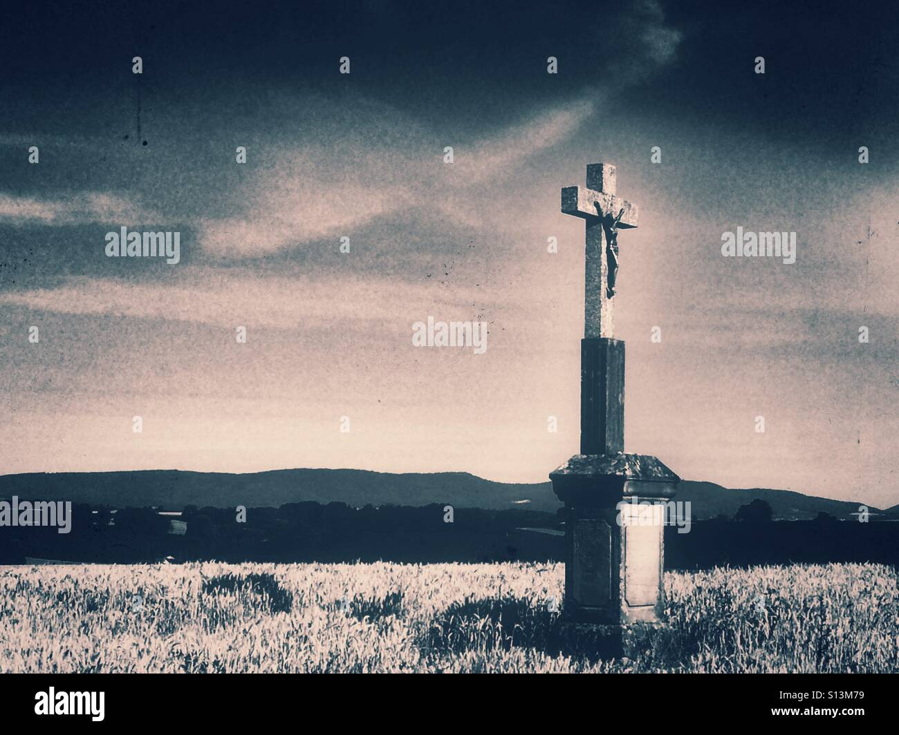Cross in a field of wheat in retro view - Stock Image