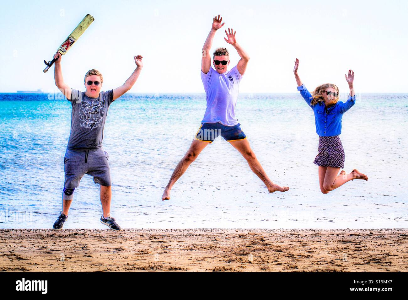 Three young teenagers having fun on a sandy beach and jumping high in the air together. - Stock Image