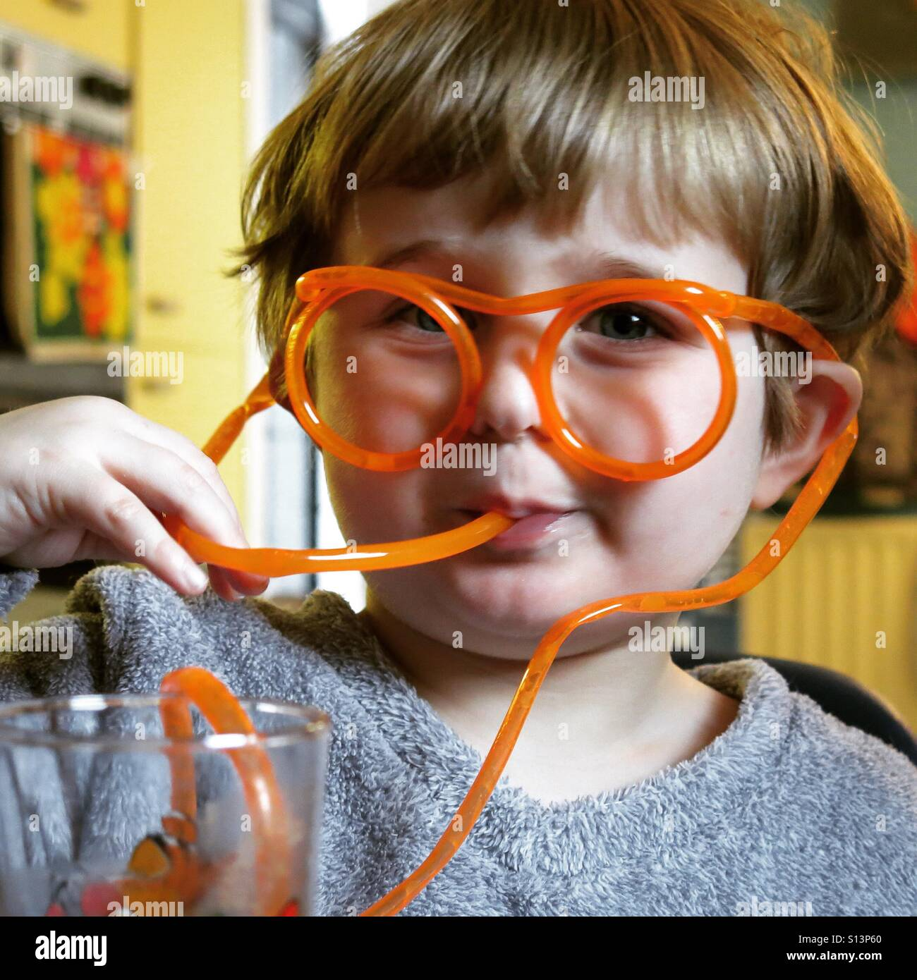A mischievous young boy wearing spectacle drinking straws looks at the camera - Stock Image
