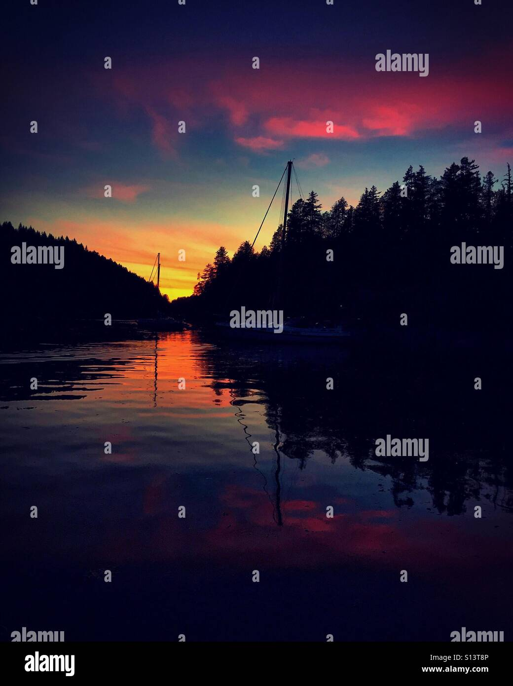 A rich and vibrant sunset fills the anchorage in Desolation Sound on a warm, summer night. - Stock Image
