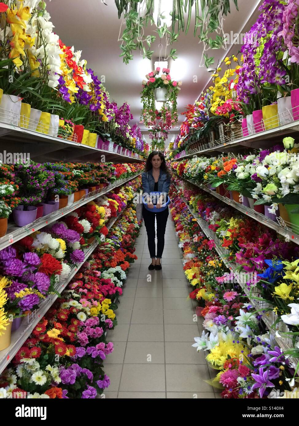 2bd9085cc3 A girl in jeans jacket standing surrounded by flowers Stock Photo ...