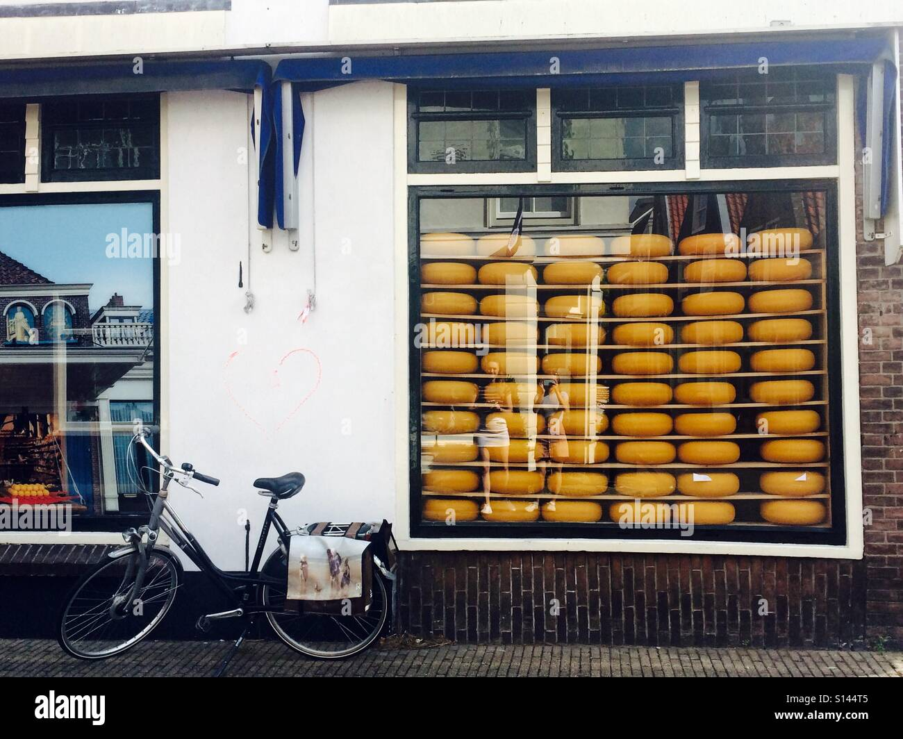 Edam cheese stacked in shop window in Edam, Netherlands. A bike rests against the wall. Yellow wax on the Edam is - Stock Image