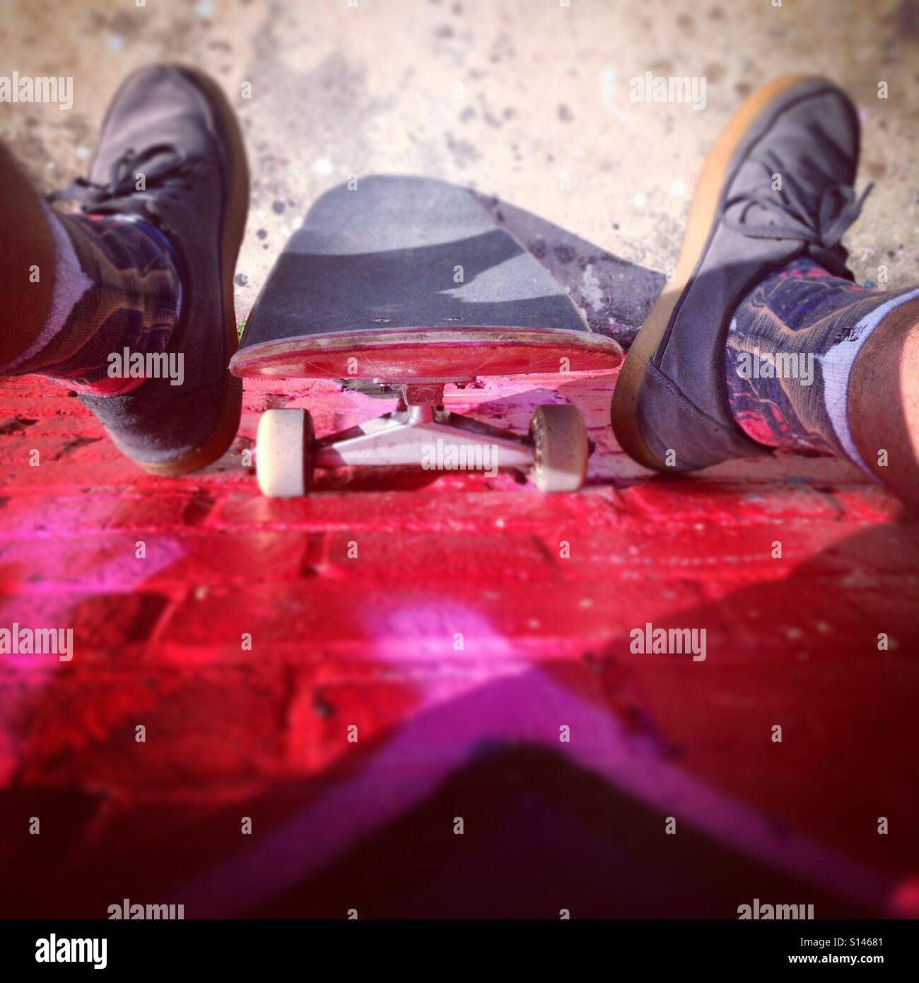Sitting on a wall at Stockwell Skatepark - London. - Stock Image