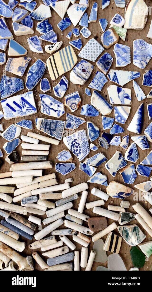 Mudlarking finds of clay pipes and pottery fragments from the sides of the river Thames, in Wapping, London. - Stock Image