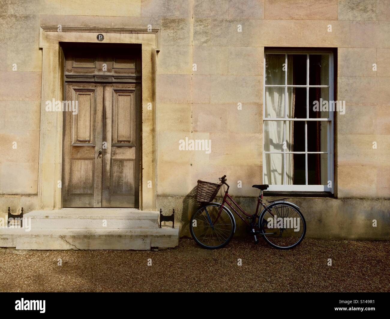 A bike rests against the wall of Downing College, Cambridge. - Stock Image
