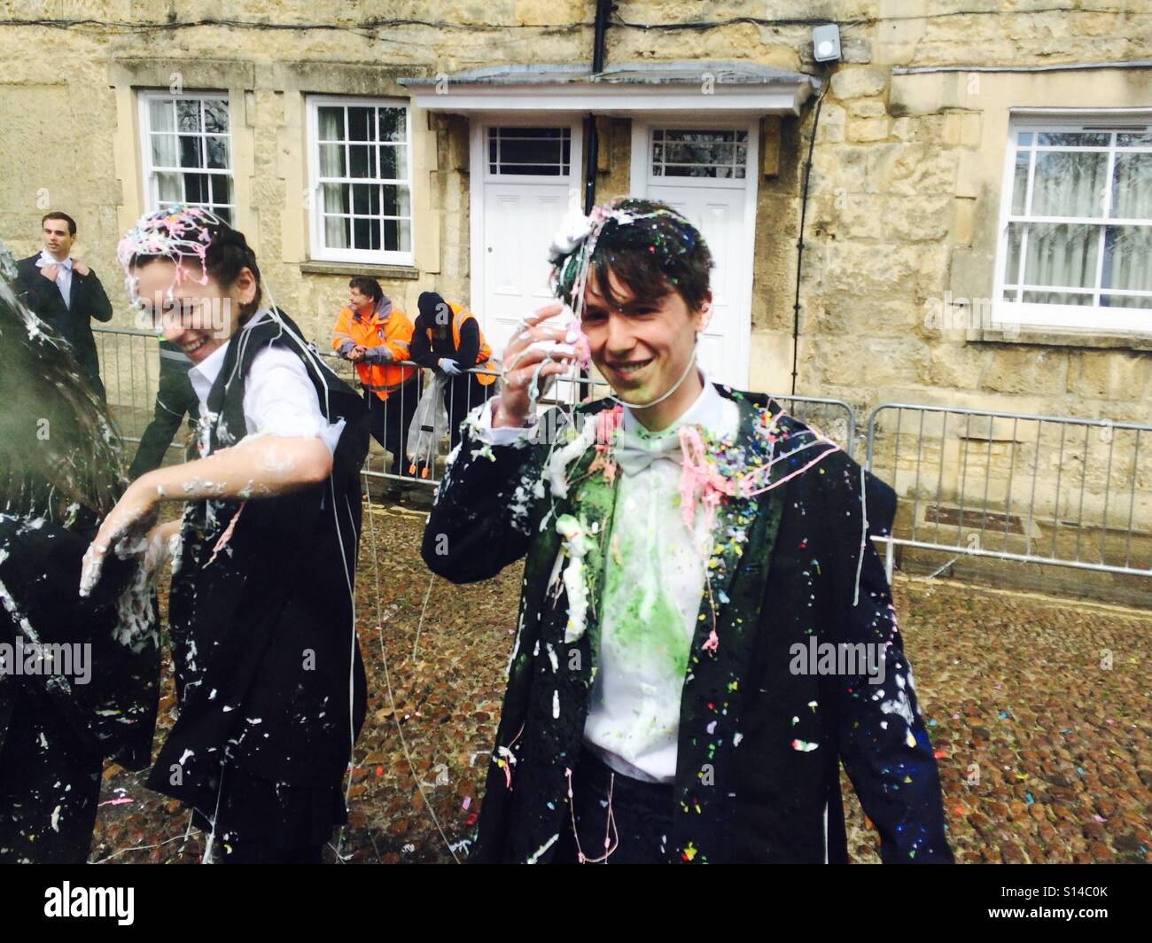 A student is covered in powder paint, silly string, confetti and champagne as he finishes his exams at the University - Stock Image