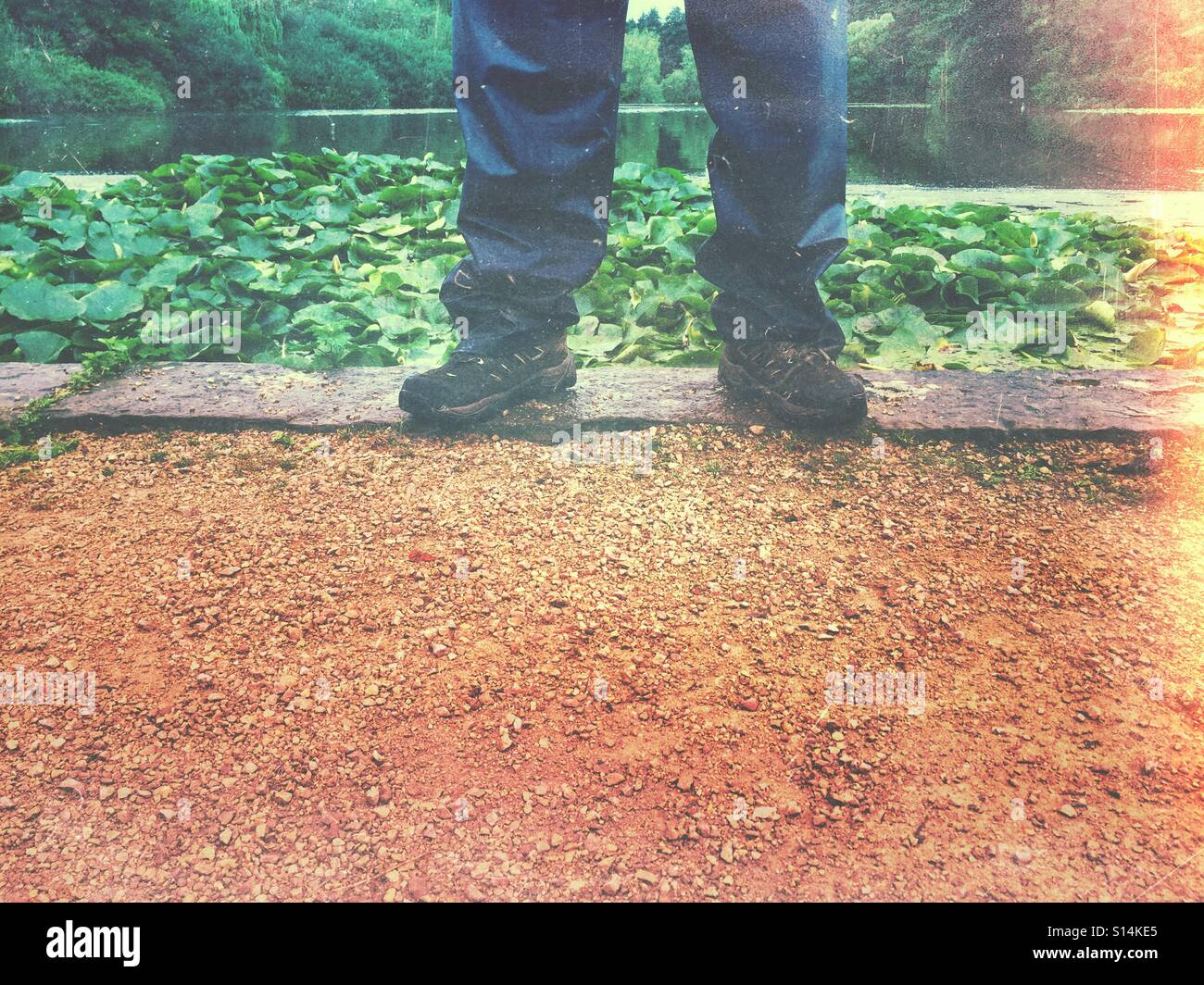 Mans legs wearing waterproof trousers and walking boots - Stock Image