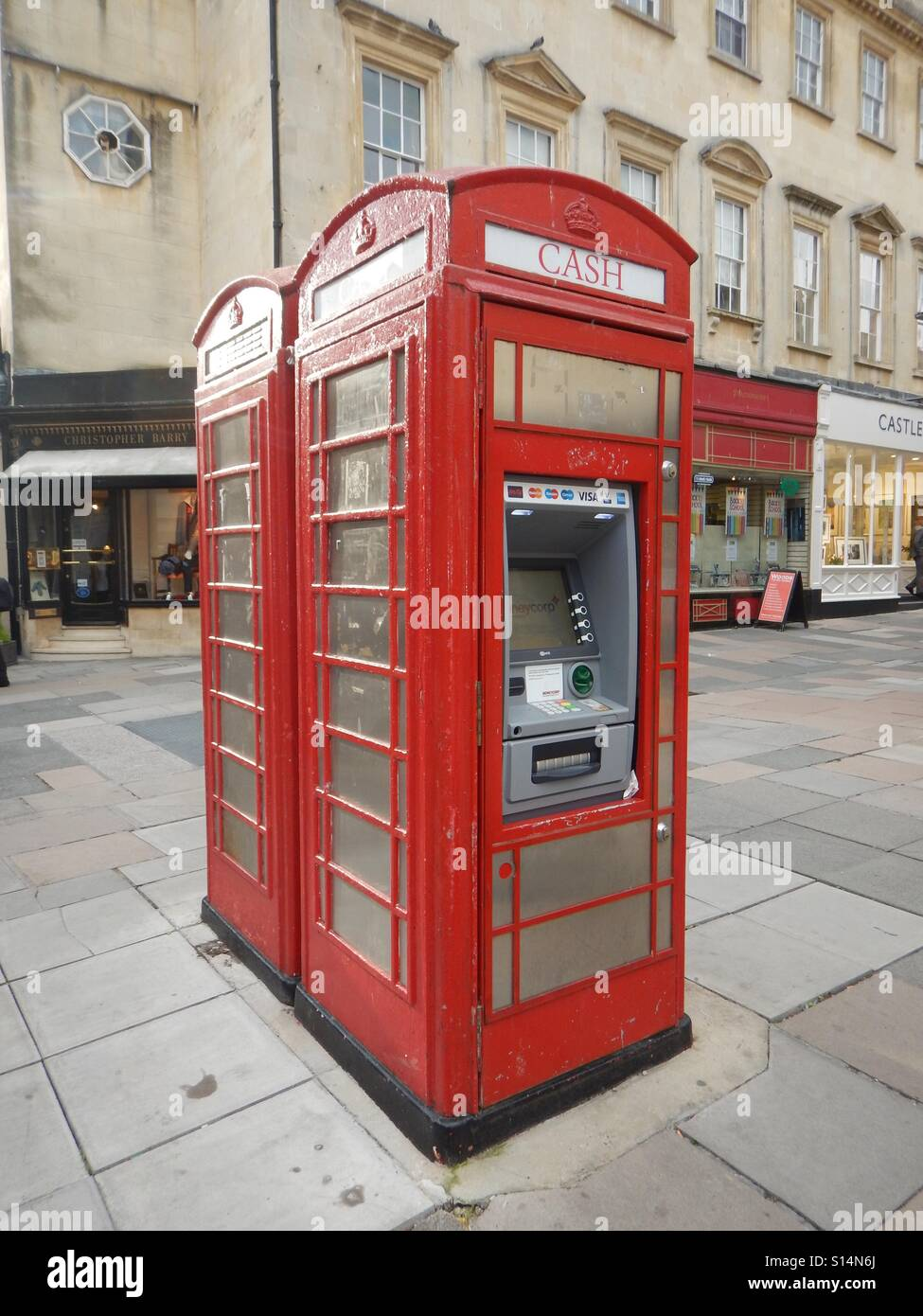 Old red telephone box in Bath, England which has been converted into a cash point machine. - Stock Image