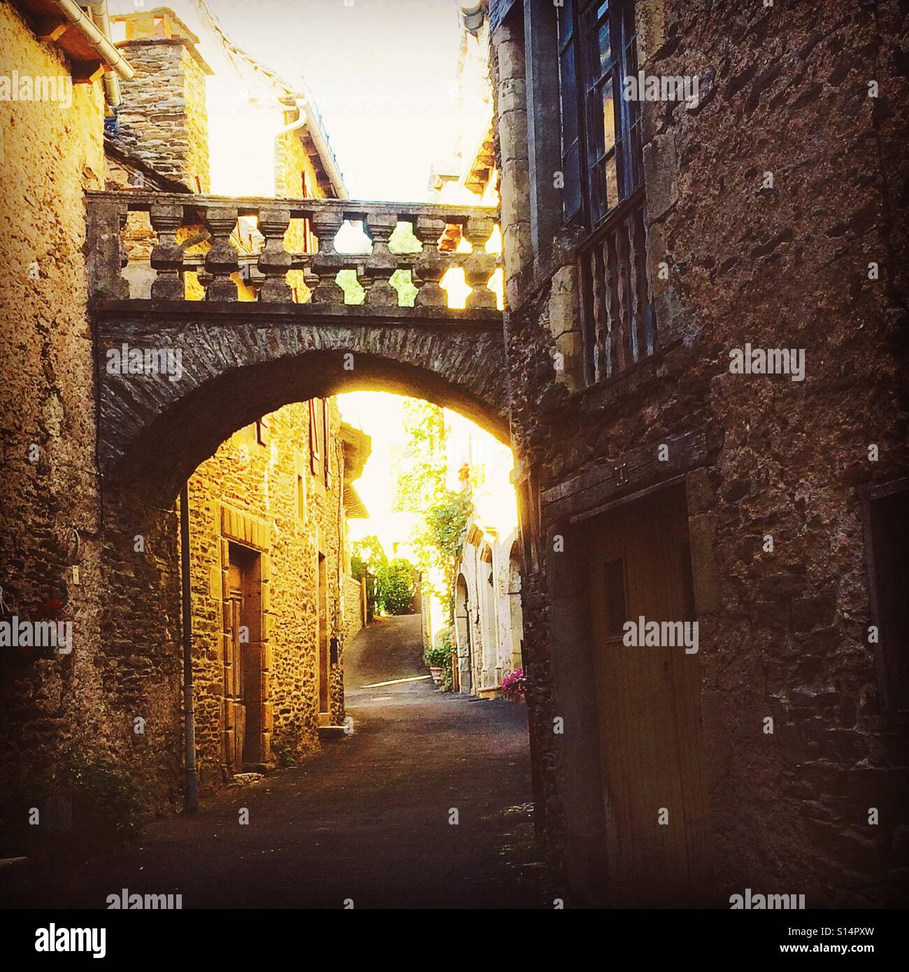 Ancient bridge in a narrow street in Estaing,France - Stock Image
