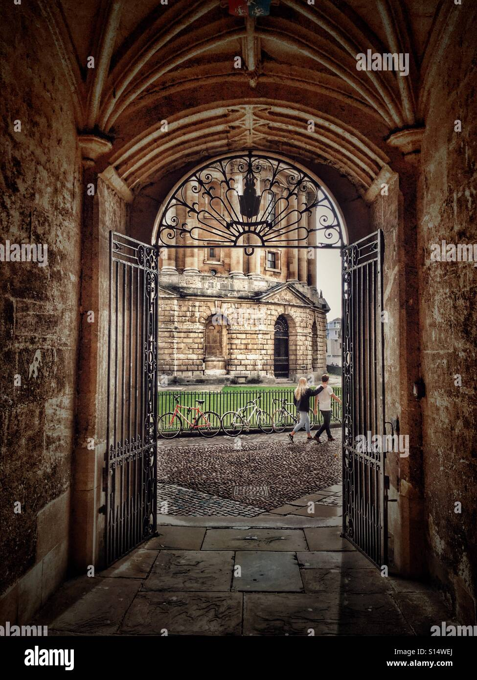 Couple walking past the Radcliffe Camera, seen through a passageway leading from the Bodleian Library, university - Stock Image