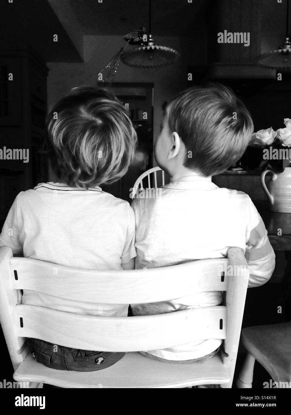 Two boys sitting next to each other on a chair - Stock Image
