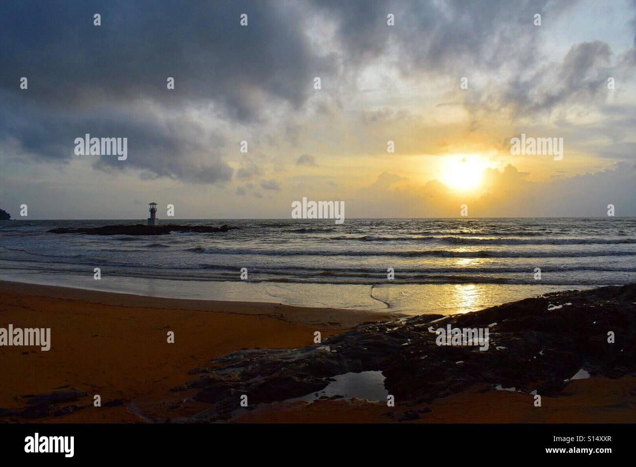 Sunset beach in Khoa Lak, on the western coast of Thailand. A lighthouse in the foreground at low tide. Captured - Stock Image