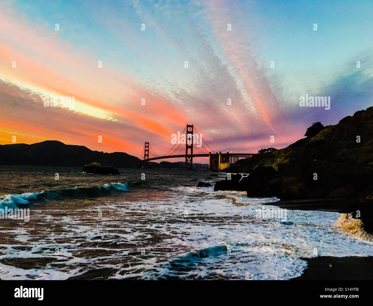 San Francisco view of the Golden Gate Bridge at sunset from Baker Beach - Stock Image