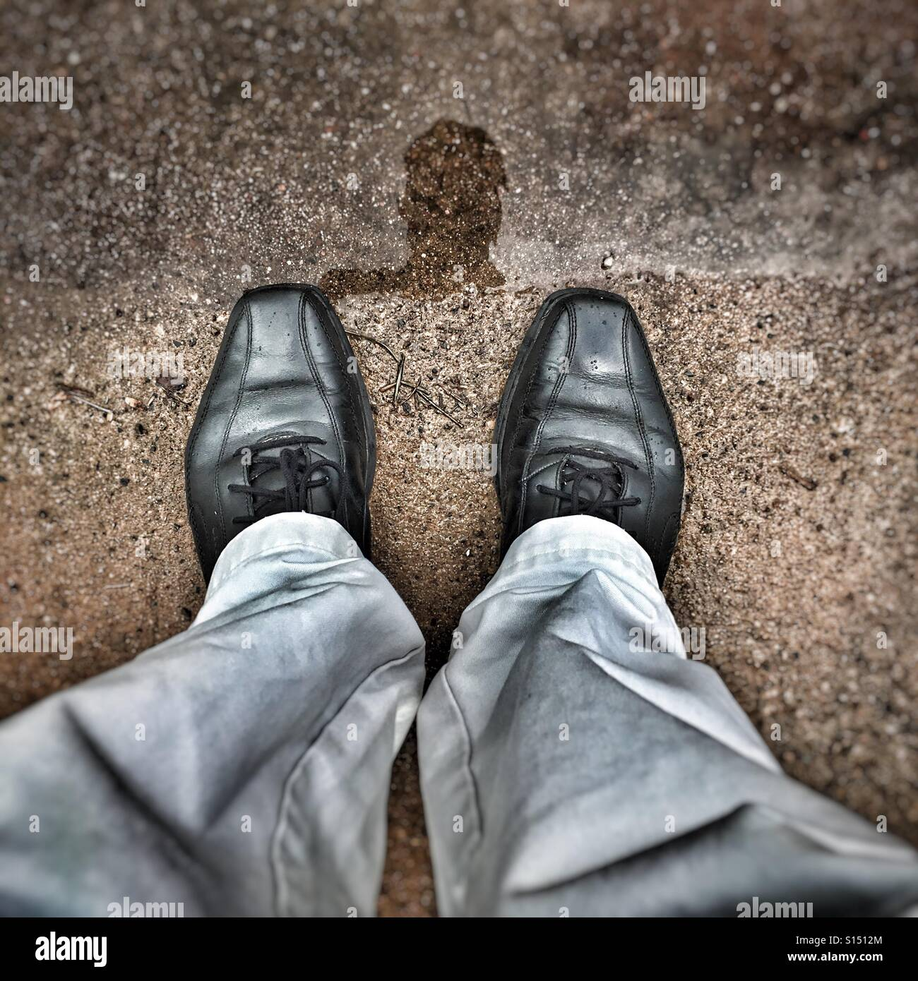 Man's feet and the reflection of his head in a puddle. - Stock Image