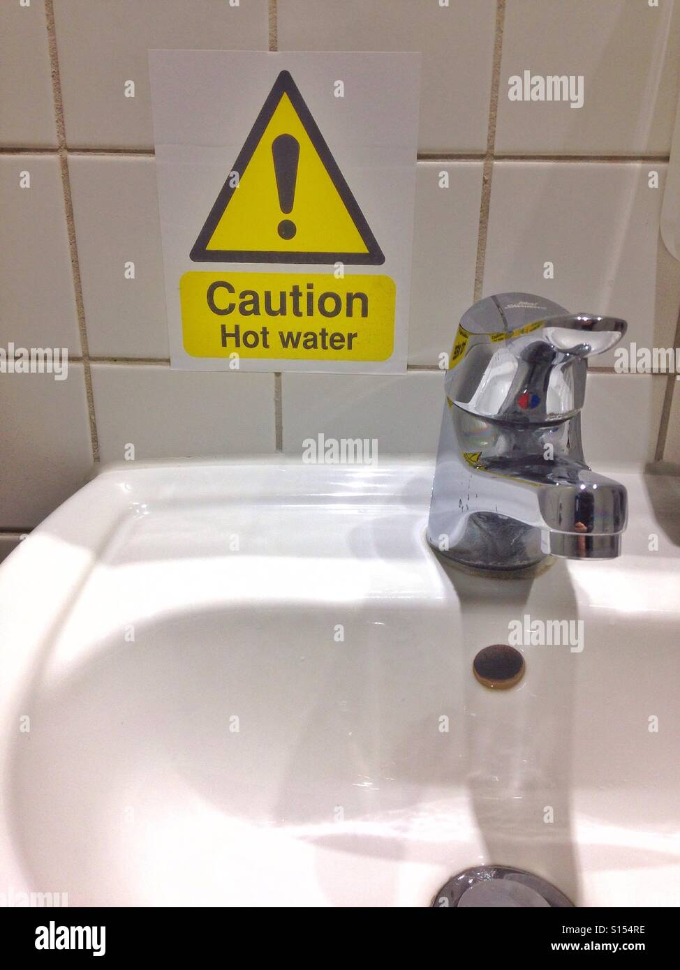 A warning label next to a sink warning that the water may be hot. - Stock Image