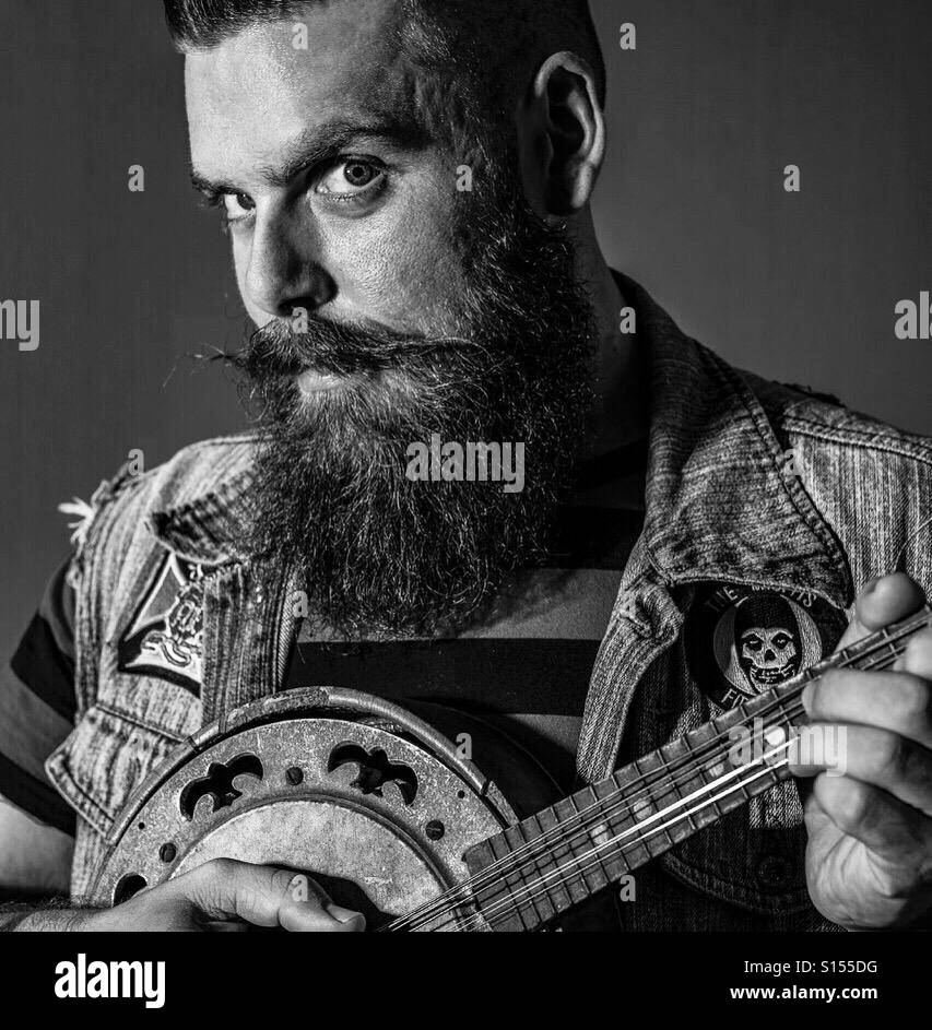 Bearded man playing ukulele in black and white - Stock Image