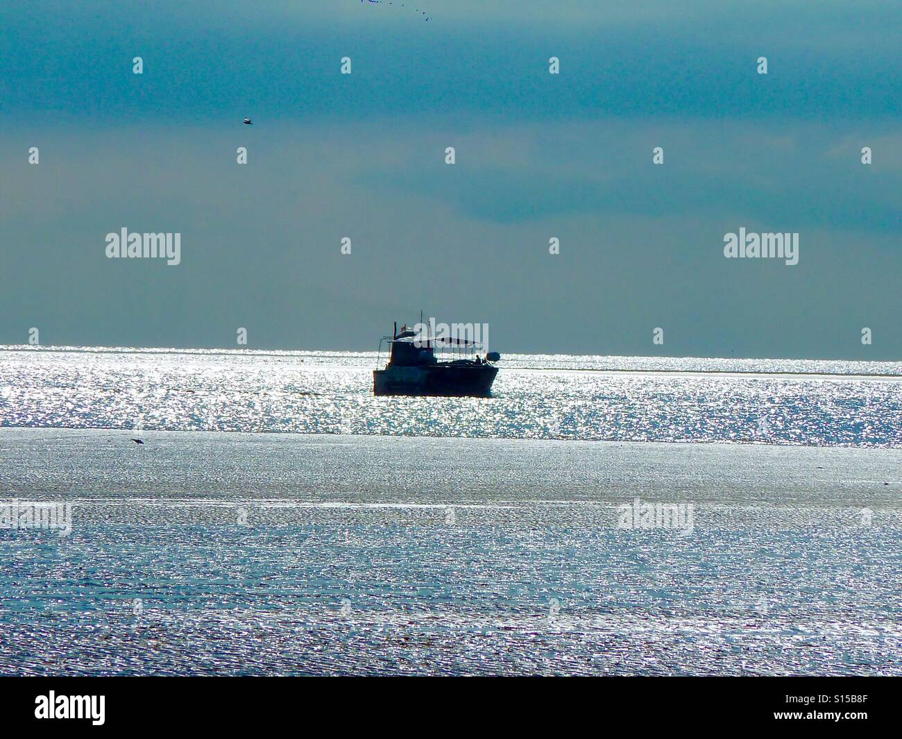 Boat on shimmering sea - Stock Image
