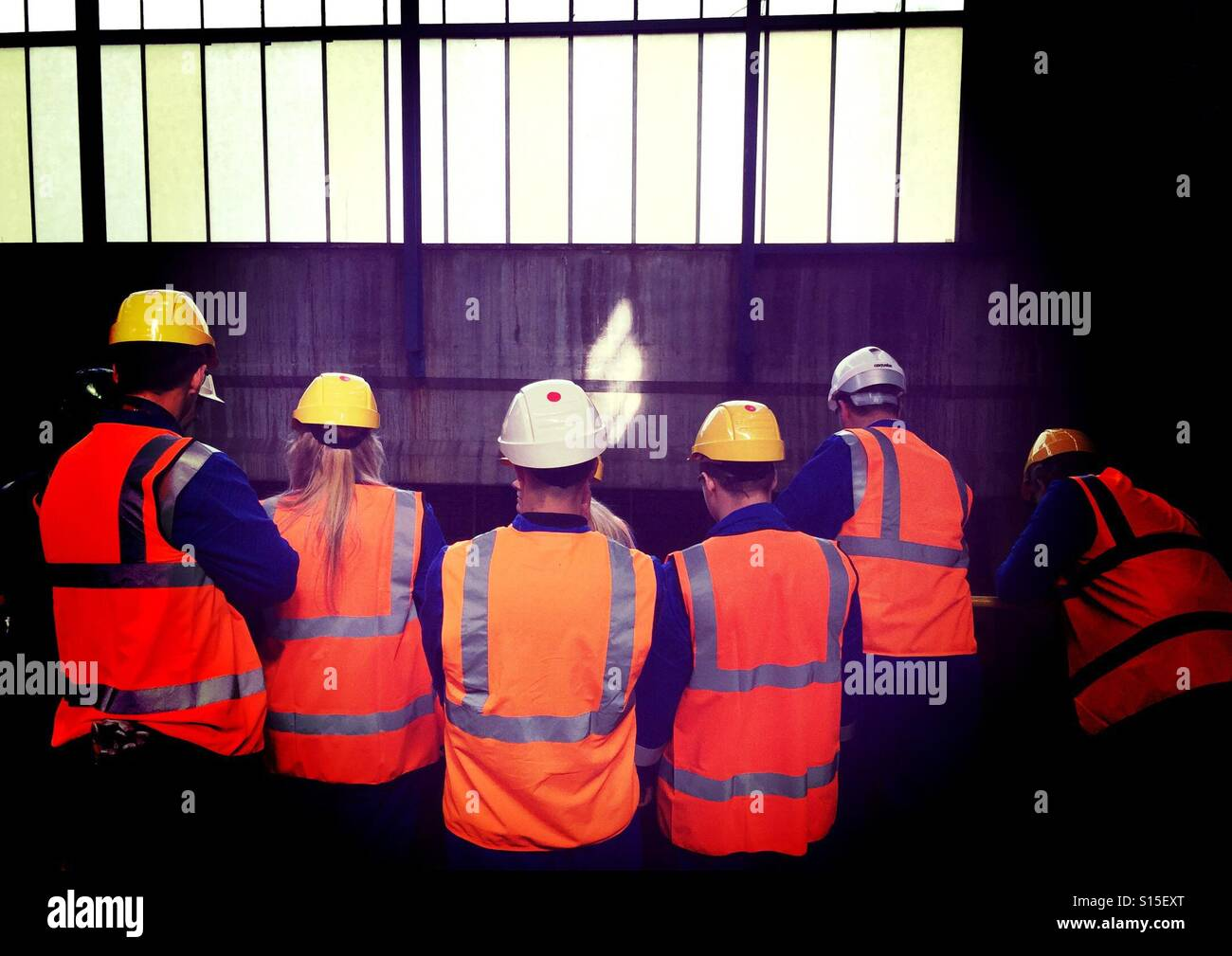 Workers in hi-viz protective clothing and jackets in industrial workplace Stock Photo