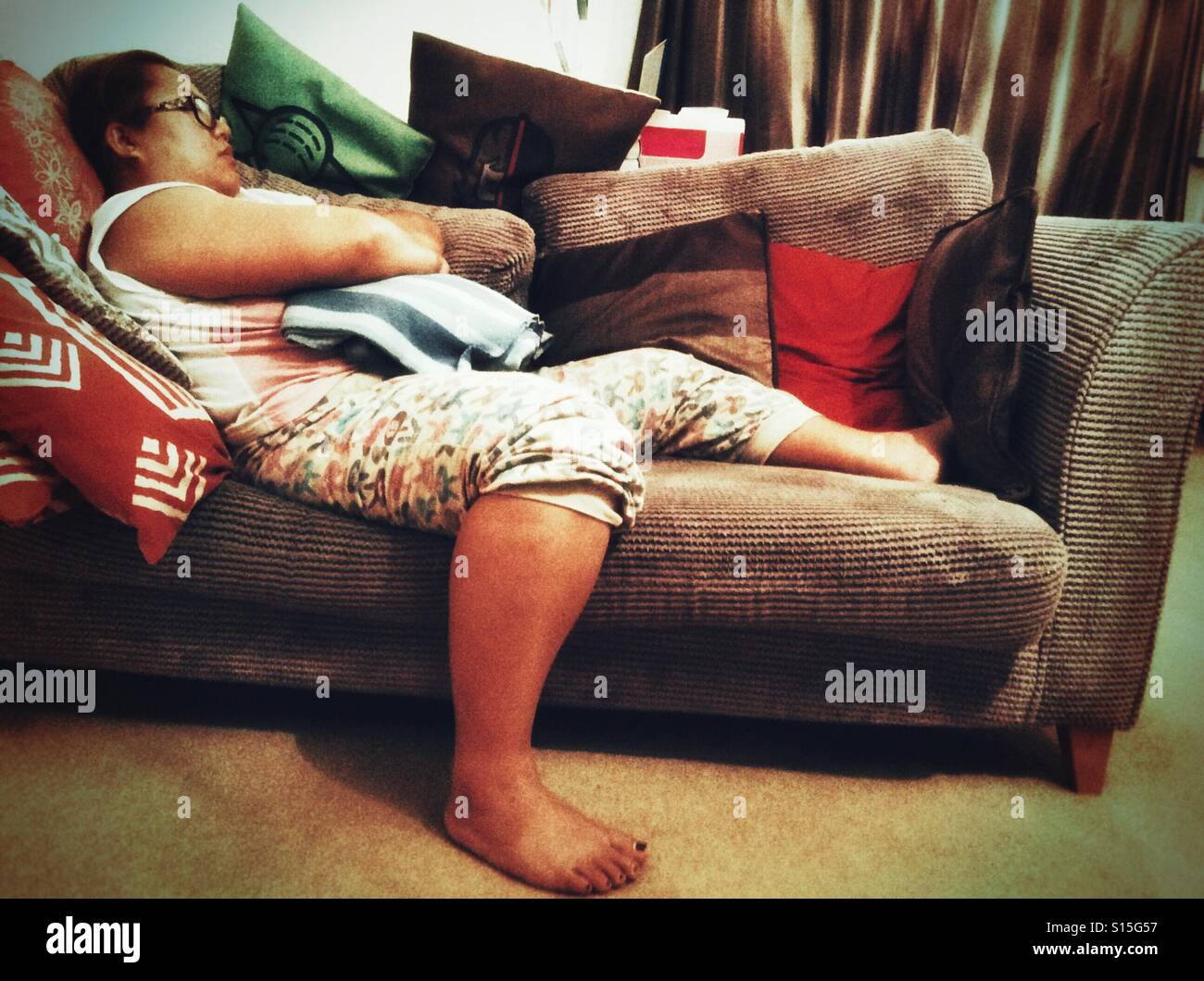 Woman asleep on a sofa. - Stock Image
