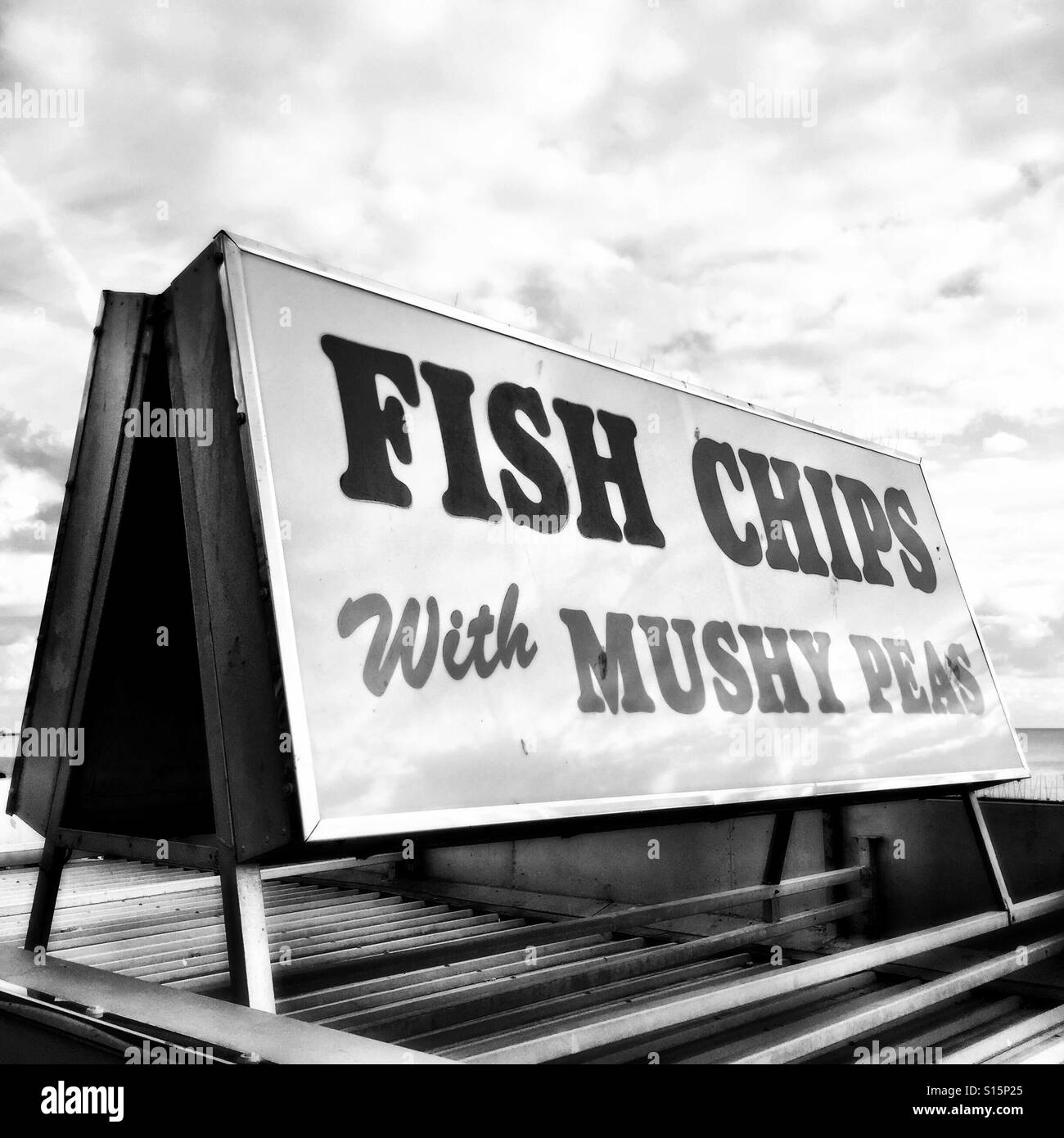 British seafront fast food sign 'FISH CHIPS With MUSHY PEAS' in black & white, Brighton, England - Stock Image