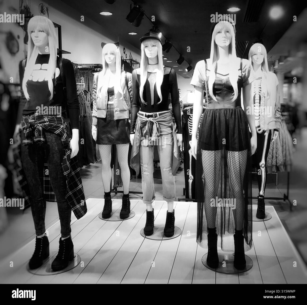 In store display of female mannequins wearing fashionable clothes - Stock Image