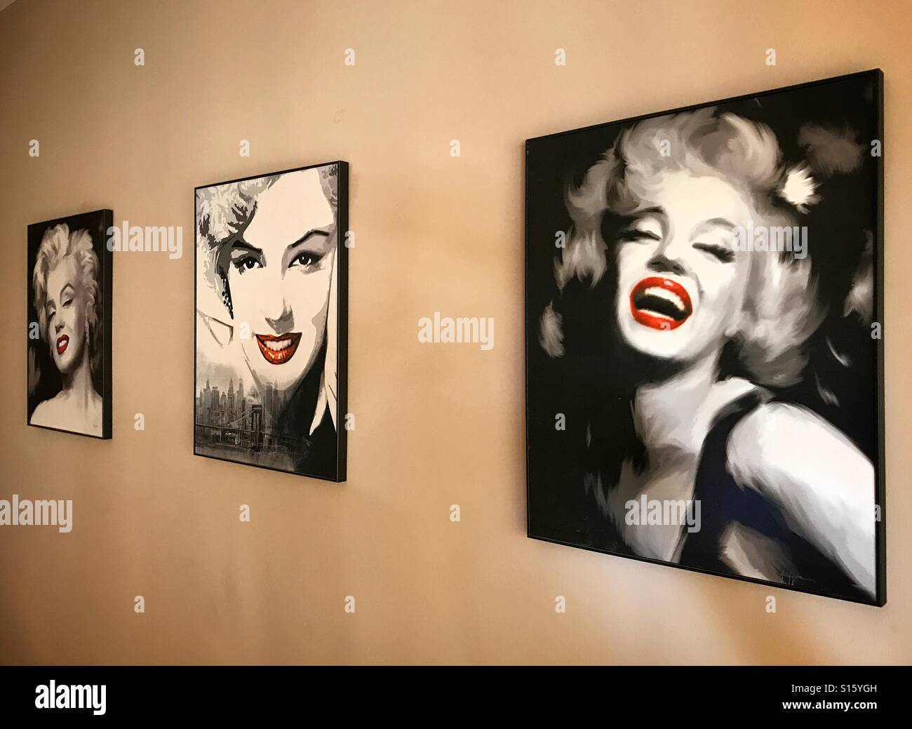 Three portraits of Marilyn Monroe on canvass displayed on the wall of a gallery - Stock Image
