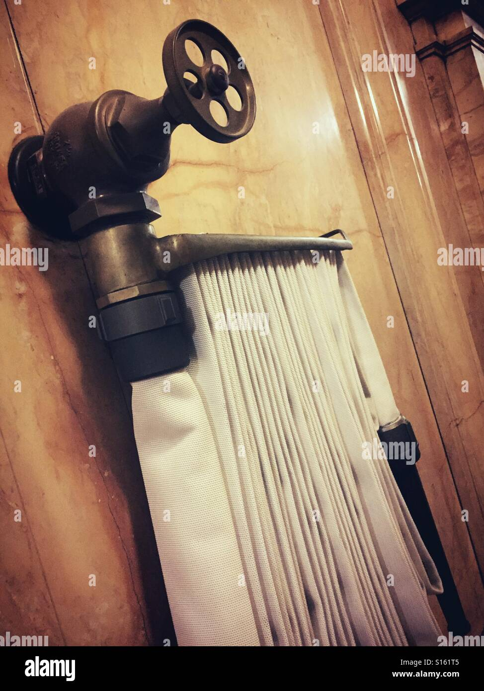 Firehose and standpipe firefighting equipment in stairwell. - Stock Image