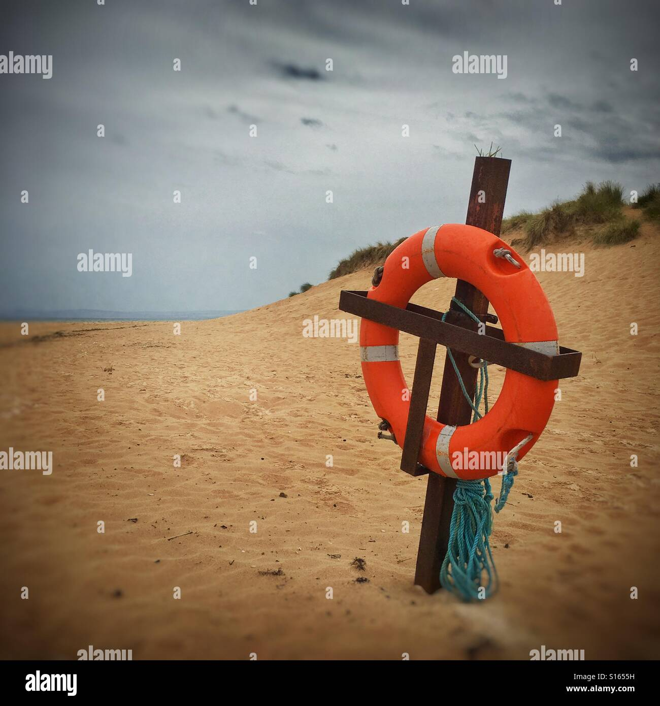 Lifebouy sitting patiently on a deserted beach at Lossiemouth, Scotland. - Stock Image