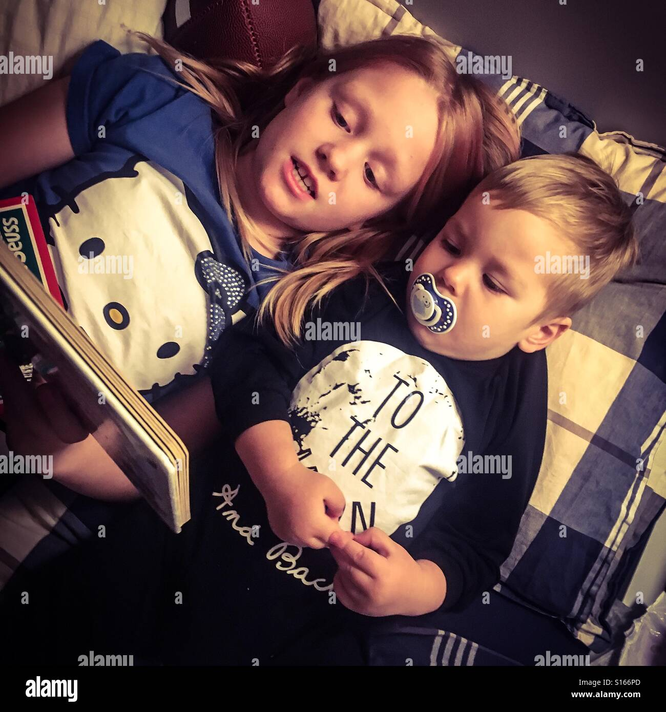 Siblings lying in bed reading a book together at nighttime Stock Photo