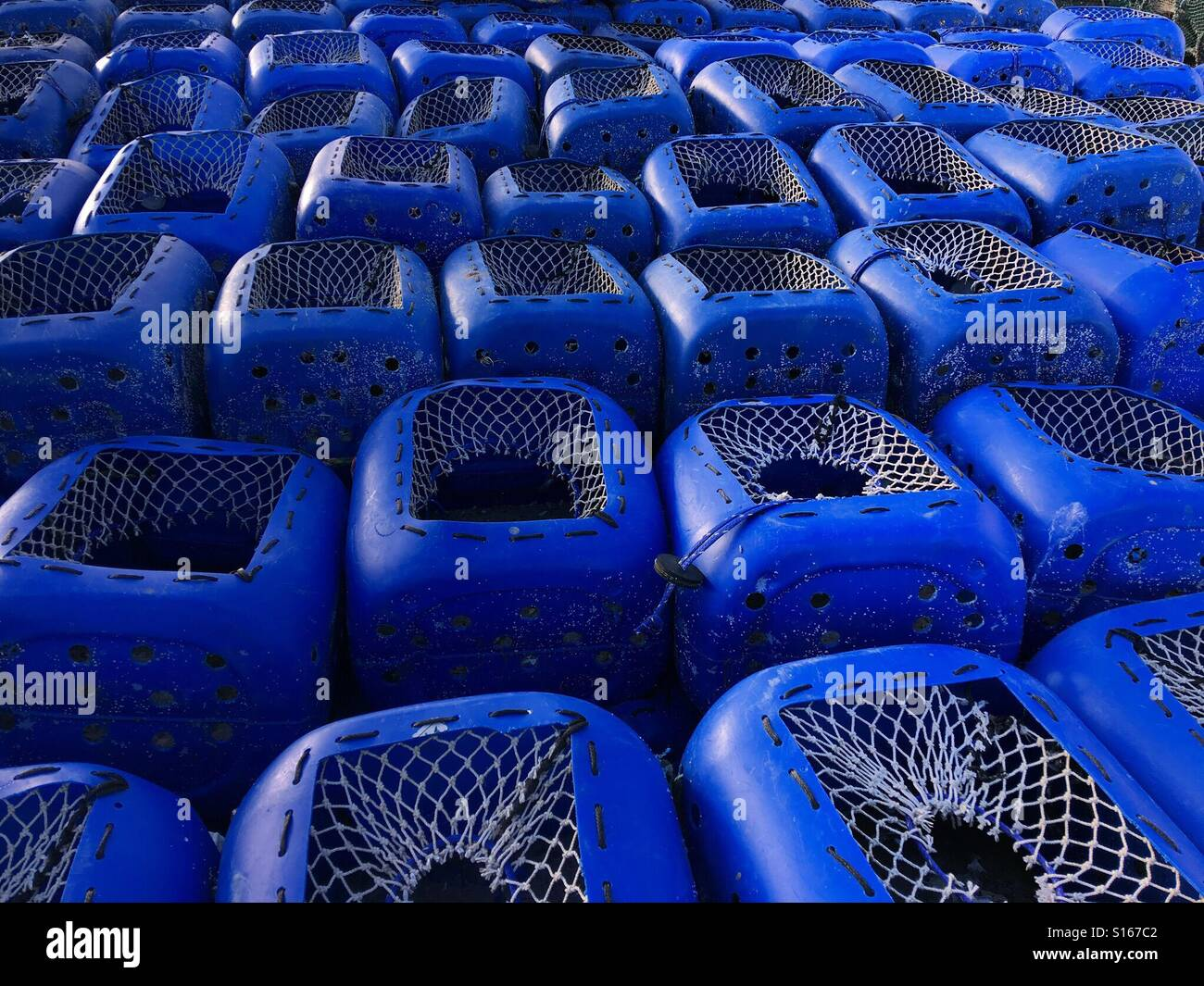 Blue plastic containers adapted to make lobster pots, stacked on the quayside - Stock Image