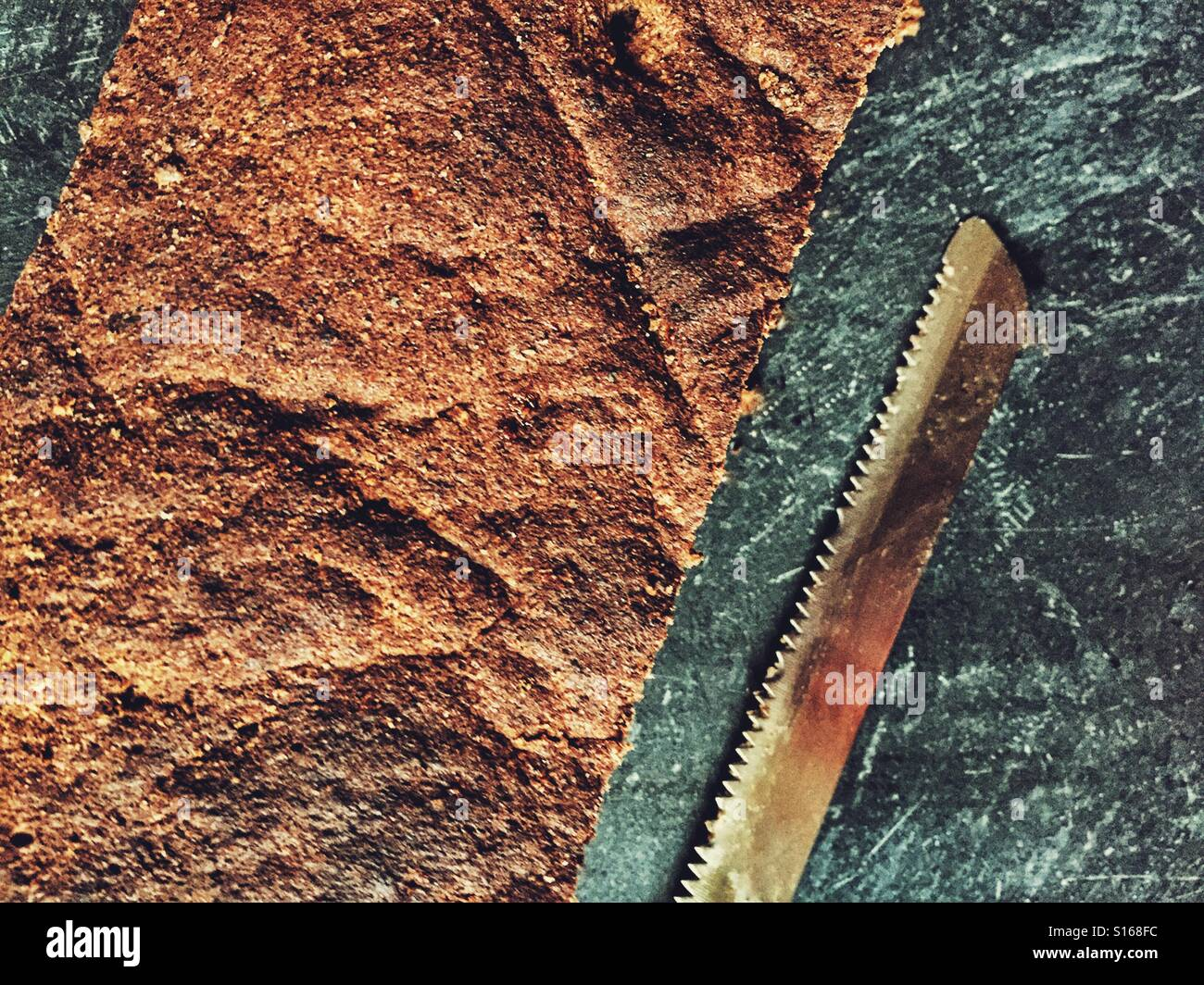 Wholewheat bread and knife on a Dark background - Stock Image