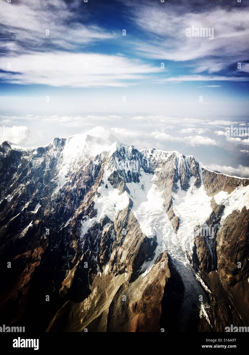 6k mountain peak surrounded by clouds - Stock Image