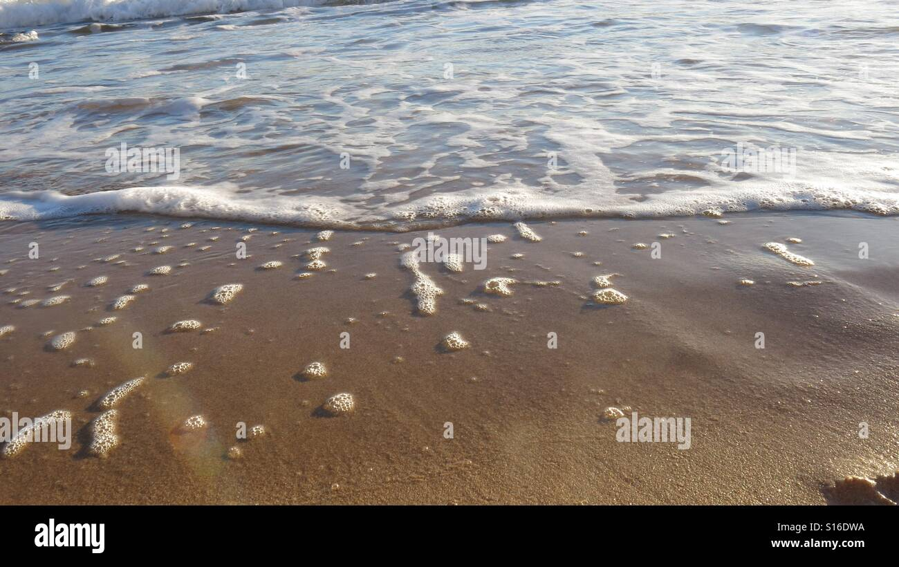 Close up of wave lapping the shore - Stock Image