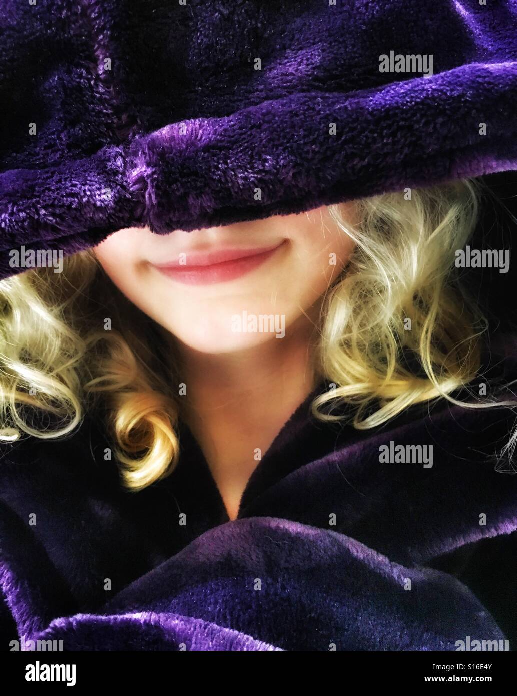 Girl snug in over sized purple dressing gown - Stock Image