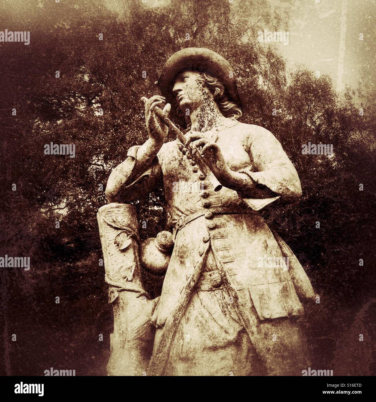 Nostalgic statue of a shepherd boy holding a pipe, in sepia tones - Stock Image