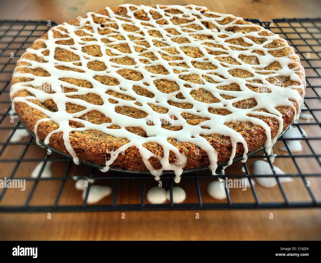 An almond poppyseed cake on a cooling rack. - Stock Image