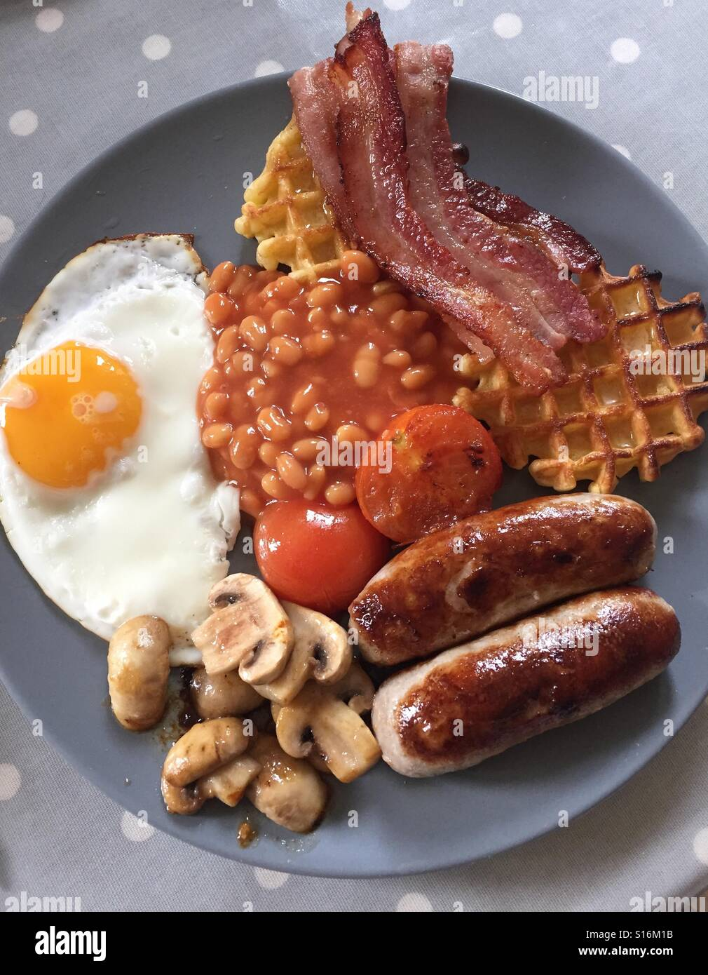 Full English Breakfast. Bacon, sausages, baked beans, tomatoes, mushrooms, egg. - Stock Image