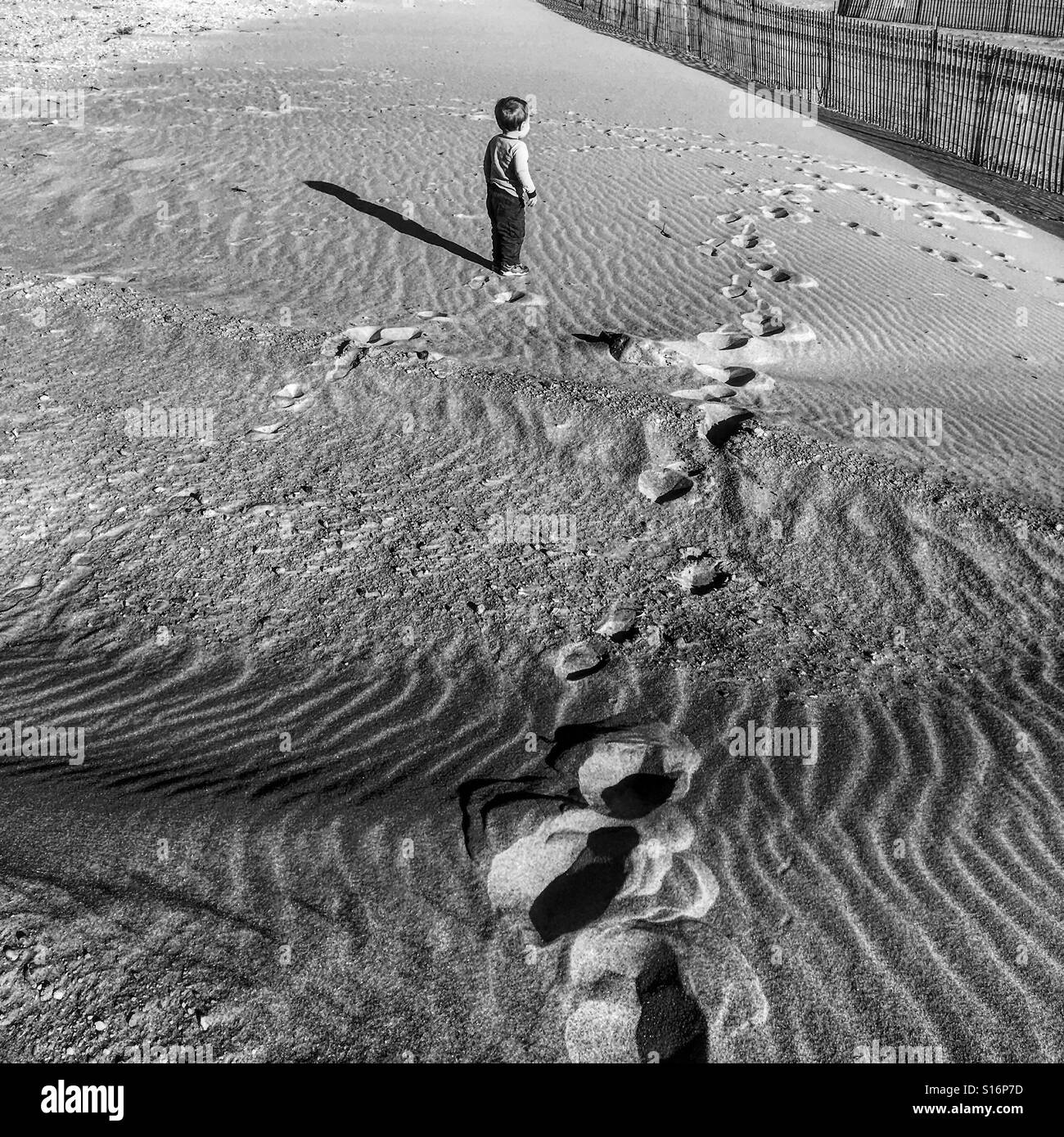 Black and white photo of a toddler boy on an empty beach in new york
