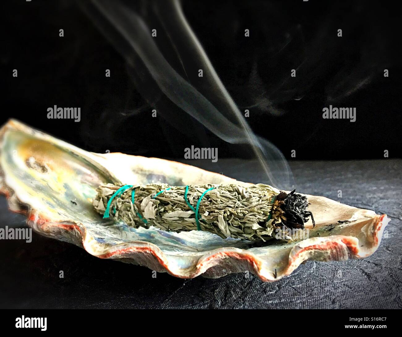 A sage smudge stick in an abalone shell. - Stock Image