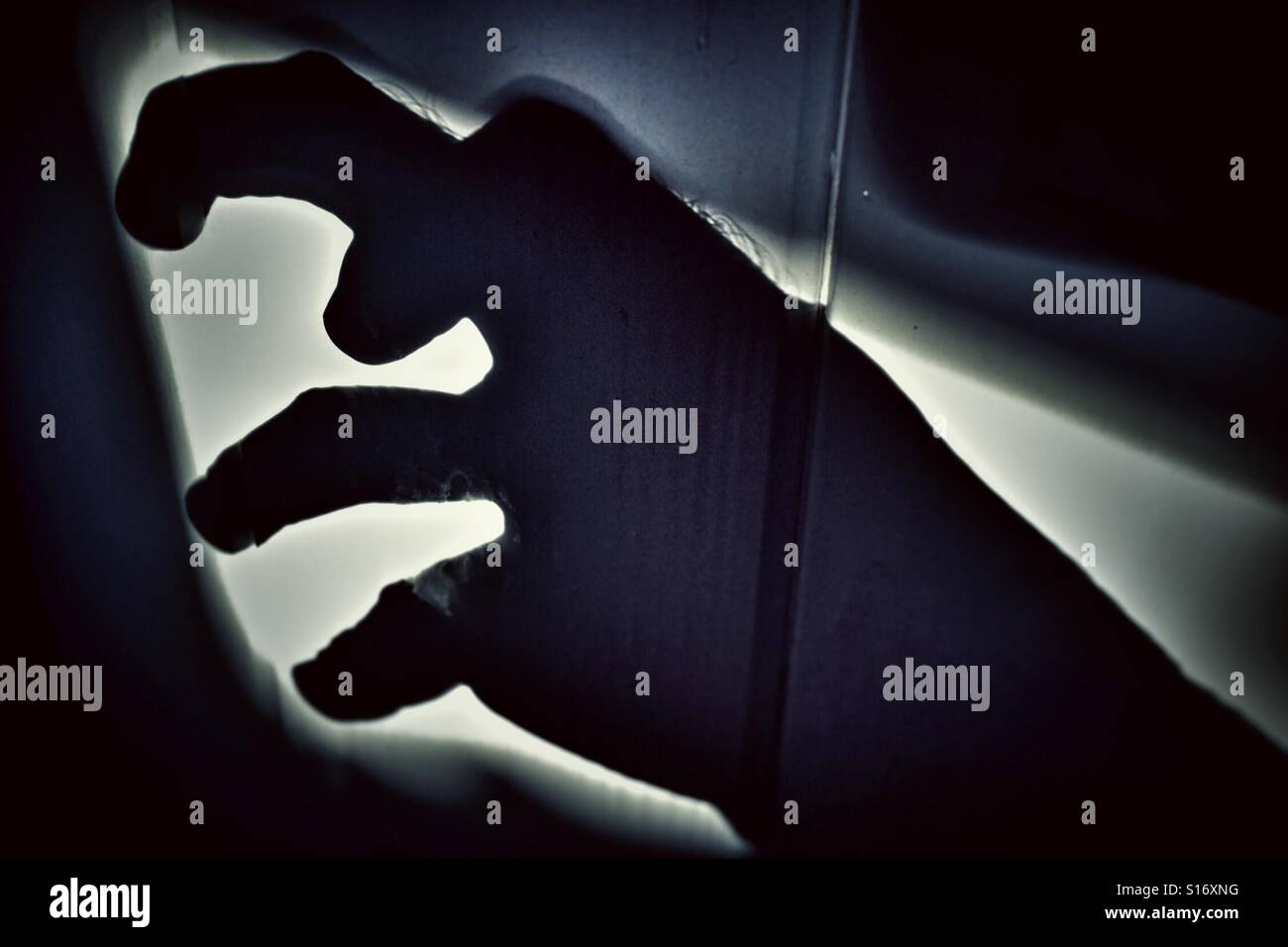 Shadow of a grabbing hand - Stock Image