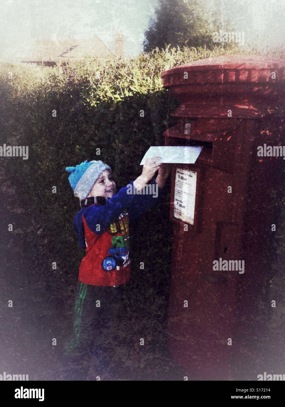 Smiling young lad posting a letter into a red postbox wearing a hat and scarf - Stock Image