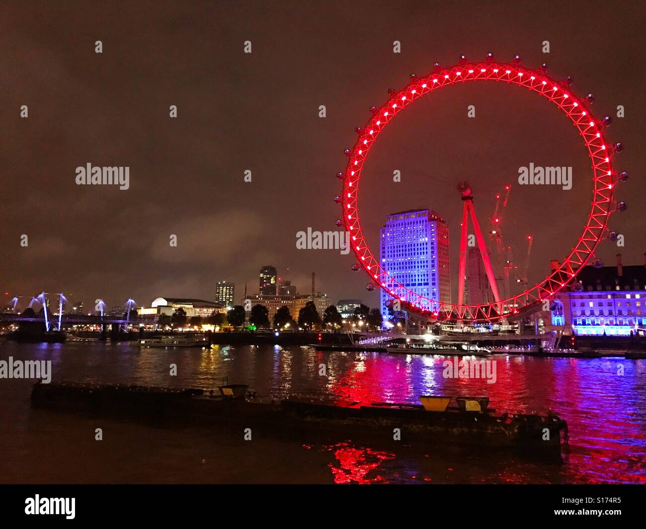 The London Eye lit up at night, from across the River Thames. - Stock Image