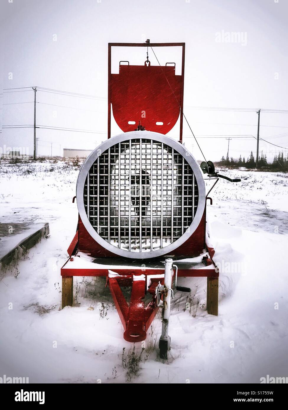 a trailer-mounted polar bear trap, baited with seal-oil-soaked canvas, stands in Churchill, Canada. - Stock Image