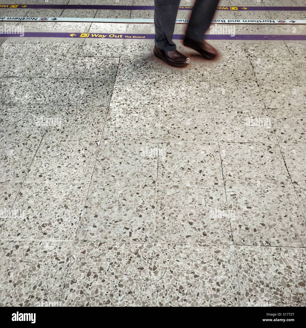 Man's feet walking across a train station concourse - Stock Image