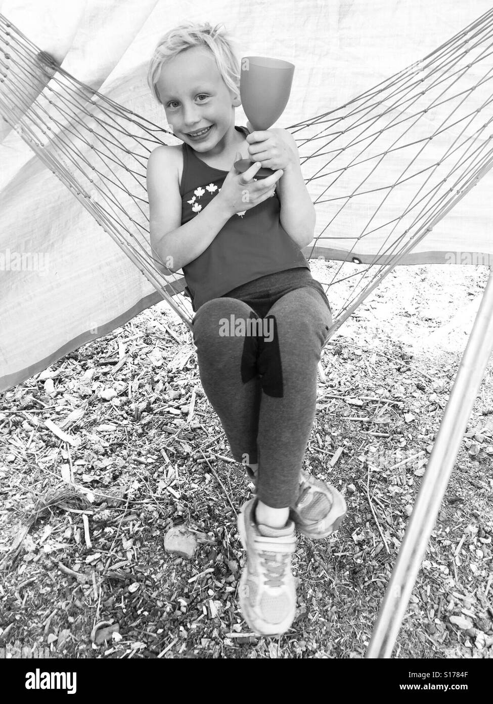 A girl in a hammock holds a drink. - Stock Image