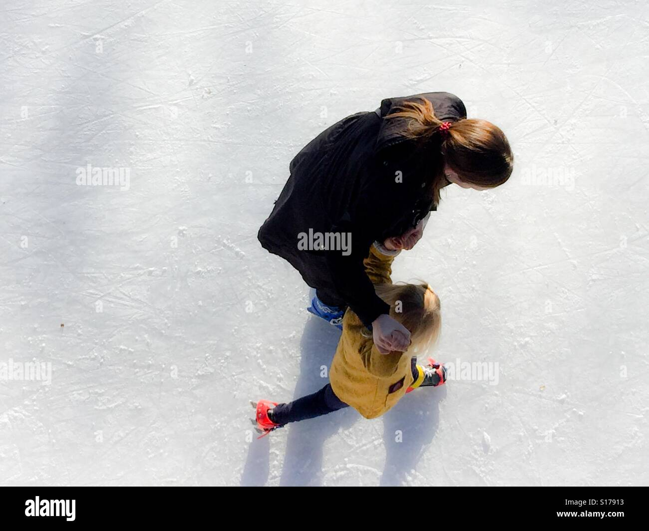 Mother teaches child ice skating - Stock Image
