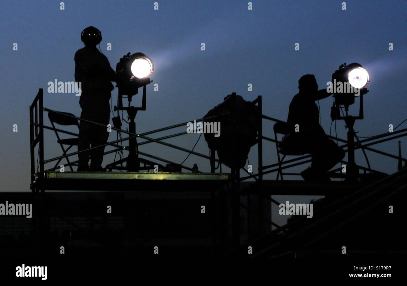 Lightning technicians on a scaffolding illuminate the stage during a music concert outdoors - Stock Image